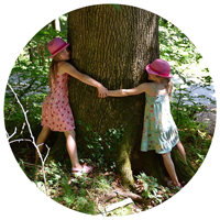 Two girls hugging a tree